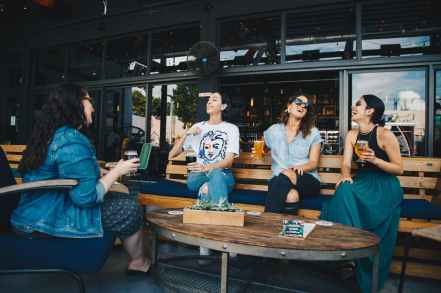 four women chatting while sitting on bench
